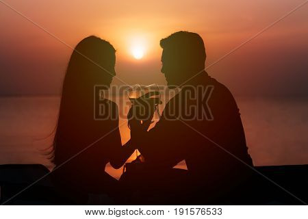 Silhouette of couple in love drinking wine during romantic dinner at sunset on the beach