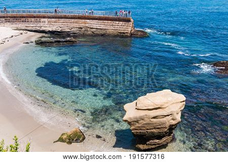 LA JOLLA, CALIFORNIA - JUNE 16, 2017:  Overlooking the La Jolla Children's Pool, with sandy beach and large rock formation, along with people enjoying the view from the seawall.