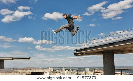 A man is jumping from roof to roof. Parkour. Active lifestyle. Courage and Adrenaline. Roofer
