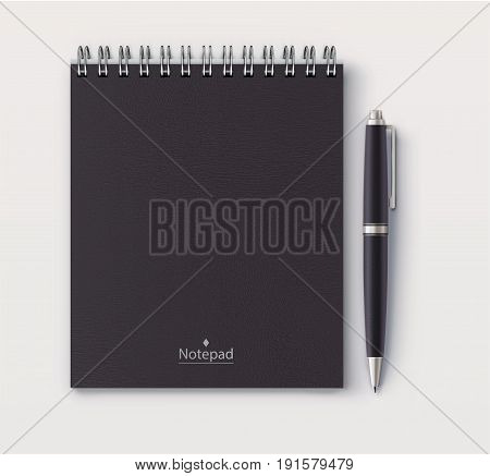 Vector illustration of top view of closed spiral black faux leather cover notebook with detailed black classic ballpoint pen on white desk background