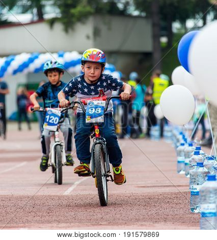 KAZAKHSTAN, ALMATY - JUNE 11, 2017: Children's cycling competitions Tour de kids. Children aged 2 to 7 years compete in the stadium and receive prizes. Portrait of three little cyclists riding their bikes.