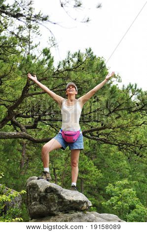 Woman hiker standing on a rock with her arms wide open