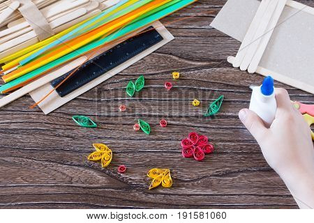 The Child Glues The Details Of The Flowers In Quilling Technique To The Gift Frame Of Wooden Sticks.