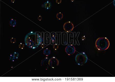 Rainbow soap bubbles on a black background