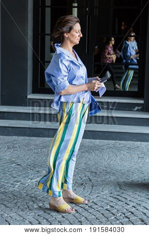 MILAN ITALY - JUNE 17: Fashionable woman poses outside Neil Barrett fashion show during Milan Men's Fashion Week on JUNE 17 2017 in Milan.
