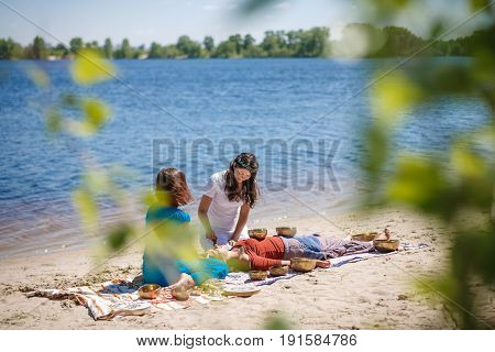 Beautiful Female Receiving Energy Sound Massage With Singing Bowls And Body Massage On A River Bank