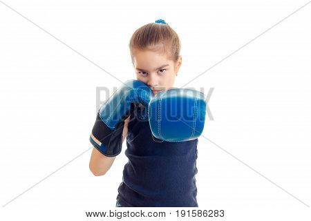 little serious girl with boxing gloves stands in front of the camera and pulls the hands isolated on white background