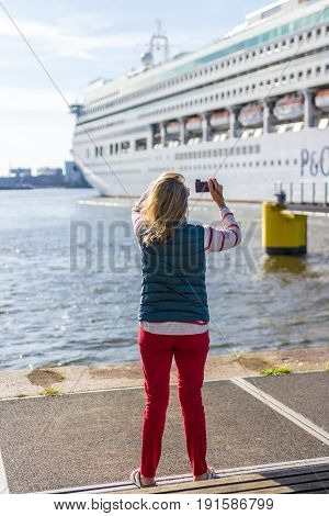 Amsterdam the Netherlands - May 31 2017: tourist taking photo of P&O Aurora cruise ship in Amsterdam