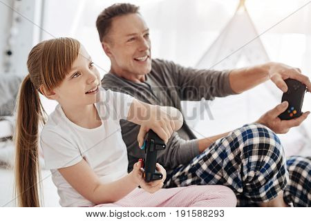 In another world. Charismatic nice beautiful family enjoying video games while spending morning at home and having fun together