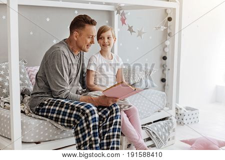 Start of the new story. Inspired amazing cool dad sitting on the bed and reading for his child while the girl listening attentively