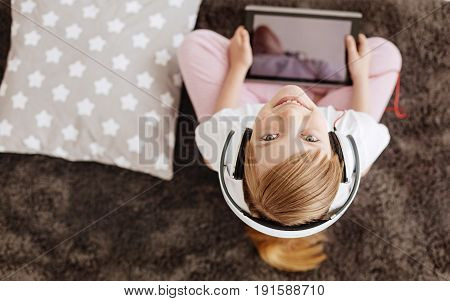 Never bored. Pretty savvy curious child sitting on a rug and holding a tablet she using for watching movies