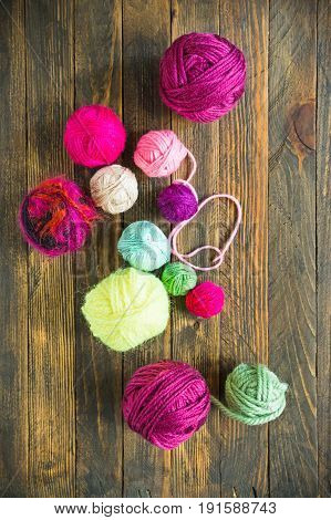 Multi-colored balls of yarn for knitting in the wooden background.