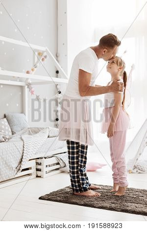My precious girl. Affectionate motivated young father encouraging his child dancing while dressing up like a ballerina and kissing her in a forehead