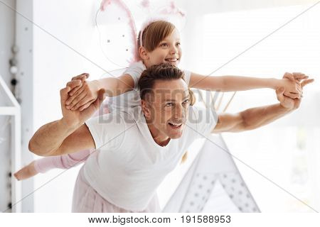 Fly away. Strong energetic positive man making his child happy by playing with her and riding her on his back