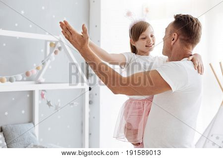 Best partner ever. Caring amazing emotional father making his daughter felling like little princess while playing with her at home