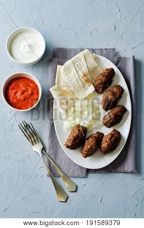 Minced meat sausage with onion sour cream pita and red bell pepper relish