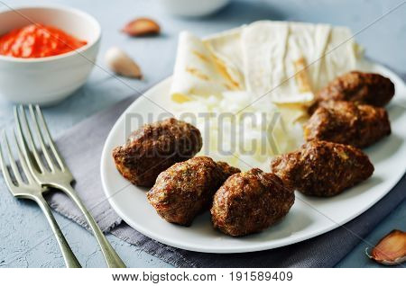 Minced meat sausage with onion sour cream pita and red bell pepper relish.