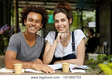 Young European Woman Wearing Jean Catsuit Helping Her African Dark-skinned Friend With Studying Whil