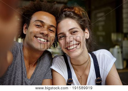 Photo Of Mixed Race Female And Male Making Selfie Having Sincere Smiles On Their Faces Rejoicing Spe