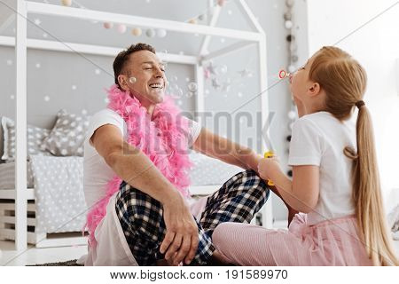 Feeling happiness. Relaxed blissful emotional man spending the weekend at home and playing with his child while enjoying his time