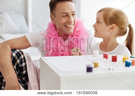 Artistic family. Original inspired optimistic father and his daughter spending their time together and preparing creating nice pictures using watercolors