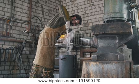 Blacksmith manually temper steel knife in engine oil, telephoto