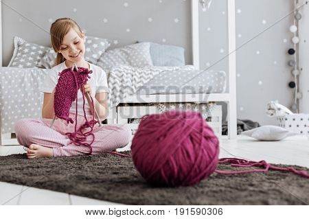 Little craftswoman. Talented dreamt persistent child feeling inspired while working on something and learning the process of knitting