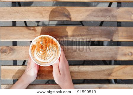 Woman holding a paper cup with coffee. Coffee to go. Tasty hot beverage on wooden table in sunny day. Outdoors meal. Flat lay top view.