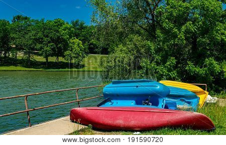Old paddle boats and a canoe by the lake