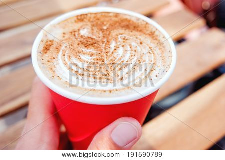 Woman holding a paper cup with coffee. Coffee to go. Tasty hot beverage on wooden table in sunny day. Outdoors meal. Close up.
