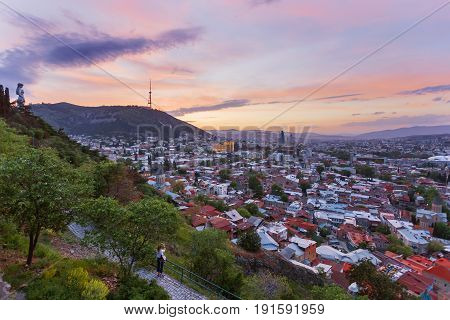 Tourist shoots sunset panorama view of Tbilisi capital of Georgia country from Narikala fortress.