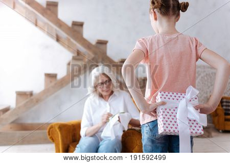Loving granddaughter. Nice pleasant cute girl holding a gift box and hiding it behind her back while preparing a surprise for her grandmother