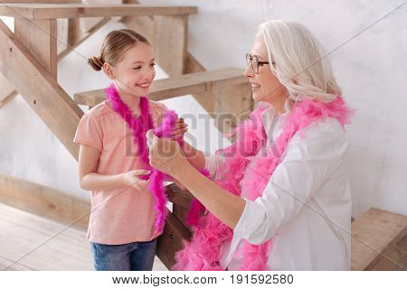 So fluffy. Nice delighted positive grandmother and granddaughter looking at each other and smiling while wearing pink feather boas