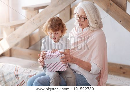 I like surprises. Joyful curious impatient boy smiling and opening his present while sitting on the grandmothers laps