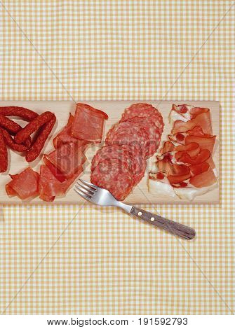cold cuts salami and ham on wooden platter