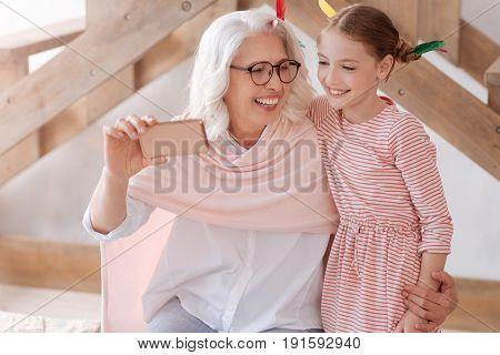 Lets take a selfie. Cheerful pleasant senior woman hugging her granddaughter and smiling while taking a selfie