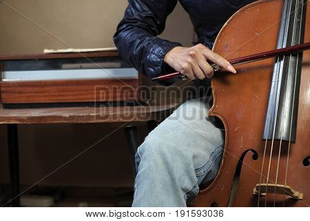 Female music student performing cello next to a retro vinyl player cropped indoor photo