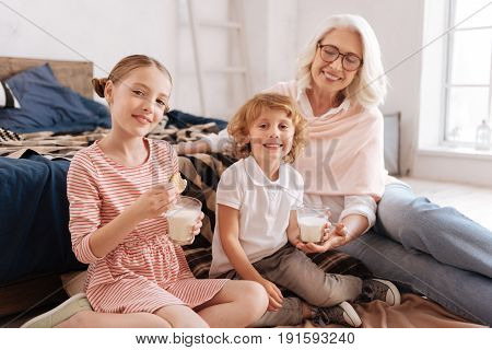 Staying healthy. Joyful nice cheerful children sitting with their grandmother and drinking milk while having lunch