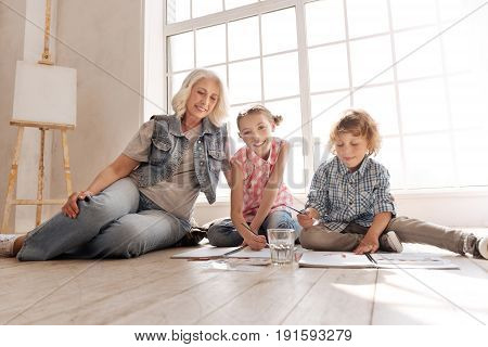 Comfortable position. Pleasant delighted nice kids sitting on the floor and painting pictured while having a great time with their grandmother