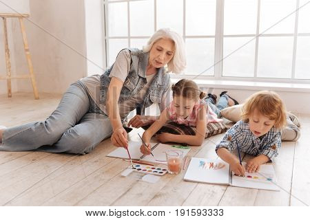 Talented children. Cute smart talented kids lying on the floor and focusing on painting while developing their talents