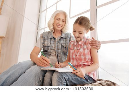 Talent and creativity. Joyful positive elderly woman sitting with her granddaughter and holding a pencil while drawing with her