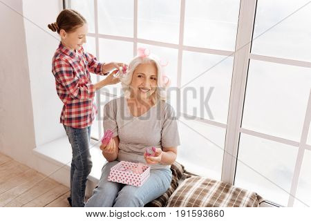 Modern hairstyle. Positive cheerful nice girl standing behind her grandmother and using hair rollers while making a hair style for her