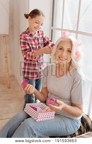 New hairstyle. Joyful senior pleasant woman holding hair rollers and smiling while being helped by her granddaughter