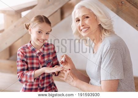 Perfect manicure. Joyful nice aged woman holding a nail varnish brush and painting her granddaughters nails while doing a manicure