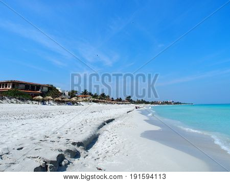 Sandy beach at Caribbean Sea in VARADERO city in CUBA with clear water on seaside landscape and exotic palms and trees, clear blue sky in 2017 warm sunny spring day, North America on March.