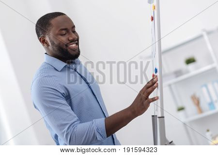 In the office. Happy nice Afro american man smiling and looking at the whiteboard while standing in the office