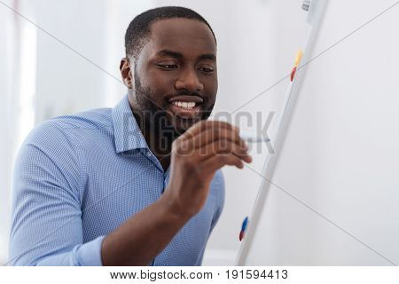 My project. Nice handsome delighted man holding a highlighter and writing on the whiteboard while presenting his project