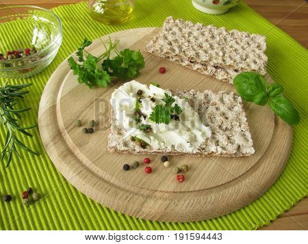 Goat cream cheese with pepper and herbs on crispbread