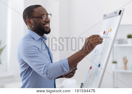 Visual presentation. Positive creative delighted man standing near the whiteboard and writing on it while presenting his report