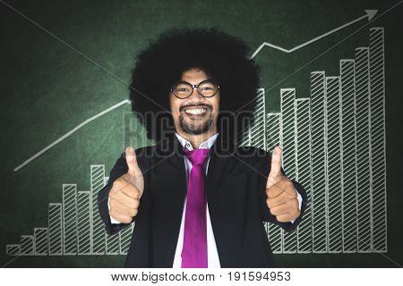 Image of cheerful Afro businessman showing thumbs up while standing with a financial graph on the chalkboard